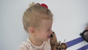 Truccatore che applica gli ombretti alla piccola ragazza graziosa video d archivio
