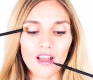 Truccatore che applica le ombre e lustro con le spazzole cosmetiche Fine in su Immagine Stock