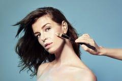 Truccatore che applica ombra sugli zigomi sul bello modello della donna Fotografia Stock Libera da Diritti