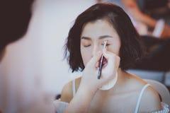 Truccatore che applica ombretto rosa al bello modello asiatico fotografie stock libere da diritti
