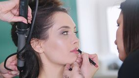 Truccatore che fa le labbra professionali di trucco per il giovane modello attraente video d archivio