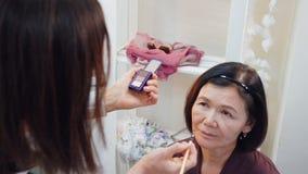Truccatore che fa le sopracciglia di trucco con la spazzola cosmetica alla donna anziana archivi video
