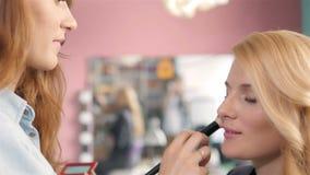 Truccatore che fa professionista della giovane donna, spazzola in mani dello stilista immagini stock libere da diritti