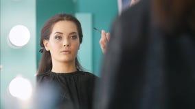 Truccatore, parrucchiere che lavora con il cliente nelle sopracciglia di modellatura e di coloritura del salone di bellezza, archivi video