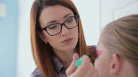 Truccatore professionista che applica mascara sui cigli del modello stock footage