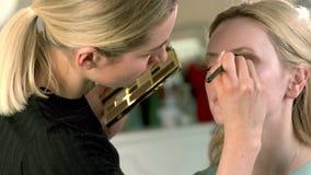 Truccatore professionista che applica trucco classico dell'occhio alla donna bionda Sguardo perfetto dell'ombretto Migliore sguar video d archivio