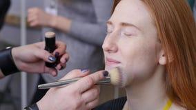 Truccatore professionista che lavora con la bella giovane donna Il modello fa il trucco dove ha dipinto le sue labbra, occhi archivi video