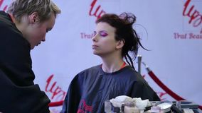 Truccatore professionista che lavora con la bella giovane donna Il modello fa il trucco dove ha dipinto le sue labbra, occhi stock footage