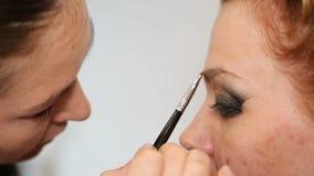 Truccatore professionista che mette i cosmetici sul fronte di modello archivi video