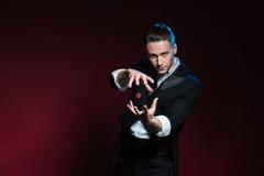 Trucchi di evocazione concentrati del mago del giovane con i dadi rossi Fotografie Stock Libere da Diritti