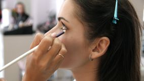Trucco applicato del truccatore delle mani sul fronte di una giovane donna Ragazza che fa trucco dell'occhio in un salone profess archivi video