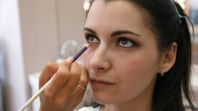 Trucco applicato del truccatore delle mani sul fronte di una giovane donna Ragazza che fa trucco dell'occhio in un salone profess video d archivio