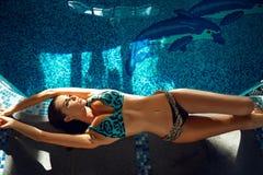 Trucco del corpo di abbronzatura della località di soggiorno dell'acqua del costume da bagno dello stagno di estate della donna Fotografie Stock Libere da Diritti