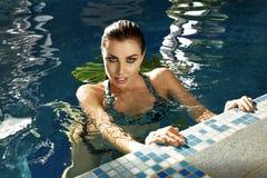 Trucco del corpo di abbronzatura della località di soggiorno dell'acqua del costume da bagno dello stagno di estate della donna Fotografia Stock