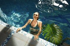 Trucco del corpo di abbronzatura della località di soggiorno dell'acqua del costume da bagno dello stagno di estate della donna Fotografie Stock