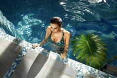 Trucco del corpo di abbronzatura della località di soggiorno dell'acqua del costume da bagno dello stagno di estate della donna Immagine Stock