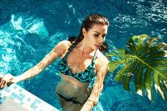Trucco del corpo di abbronzatura della località di soggiorno dell'acqua del costume da bagno dello stagno di estate della donna Immagini Stock