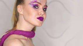 Trucco di bellezza Trucco porpora e chiodi luminosi variopinti Bello ritratto del primo piano della ragazza video d archivio