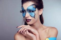Trucco di modo. Ritratto della donna di arte del fronte della farfalla. immagine stock libera da diritti