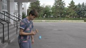 Trucco di prova di kendama dell'equilibrio del confine dell'adolescente che equilibra il bastone della punta sulla palla all'aper stock footage