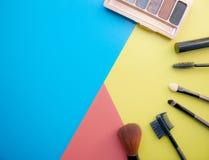 Trucco e spazzole di trucco, ombretti su un fondo colorato cosmetici per il fronte Con spazio vuoto a sinistra fotografie stock