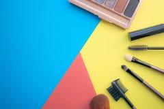 Trucco e spazzole di trucco, ombretti su un fondo colorato cosmetici per il fronte Con spazio vuoto a sinistra immagine stock libera da diritti