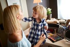 Trucco femminile del bambino la sua mamma immagini stock