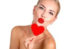 Trucco luminoso della bella donna di C e cuore rosso fotografia stock
