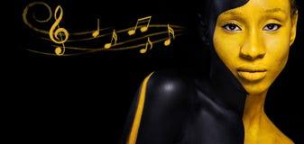 Trucco nero e giallo Giovane donna africana allegra con trucco e le note di modo di arte Pittura variopinta sul corpo immagini stock libere da diritti