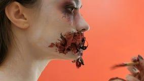 Trucco per la celebrazione di Halloween Spazzoli nella mano di un truccatore The che la ragazza disegna una bocca sanguinosa dell archivi video