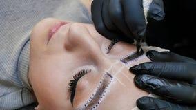 Trucco permanente Tatuaggio permanente delle sopracciglia L'applicazione del cosmetologo permanente compone sul tatuaggio del sop immagini stock