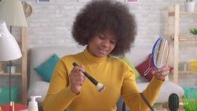 Trucco positivo della donna afroamericana che guarda nello specchio in appartamento moderno Mo lento video d archivio