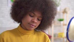 Trucco positivo della donna afroamericana del ritratto che guarda nello specchio in appartamento moderno Mo lento video d archivio