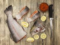 Trucha arco iris noruega fresca con el caviar del limón, la sal del mar, el cuchillo y las cebollas rojos en un fondo de madera Fotos de archivo