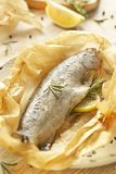 Trucha cocida al horno en el pergamino con el limón y el ro Imagen de archivo