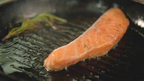 Trucha de color salm?n de la receta del cocinero de los pescados que fr?e la cacerola asada a la parrilla metrajes