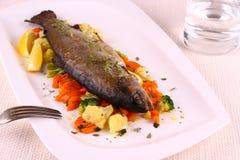 Trucha entera frita, verduras, limón, agua imagen de archivo