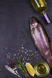 Trucha fresca cruda, botella del vino blanco, limón e hierbas en fondo de piedra gris de la textura Visión desde arriba, tiro sup Imagen de archivo libre de regalías