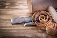 Trucioli arricciati degli scalpelli più costanti del martello del grumo sul bordo di legno d'annata Immagine Stock Libera da Diritti