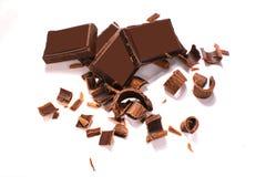 Trucioli e pezzi neri deliziosi del cioccolato su fondo bianco, vista superiore fotografia stock libera da diritti