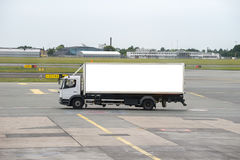 Truck on airport runway. White truck driving across airport runway Stock Image
