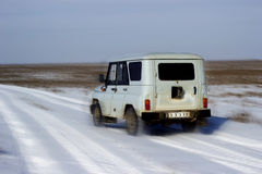 Truck all-terrain. Passenger car with high cross moves across the steppe in winter Stock Photography