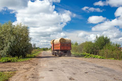 Truck with bales of hay rides on the road Royalty Free Stock Image