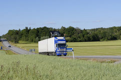 Truck in beautyful country sur. Blue/white clean truck driving on country road in summer time Stock Images