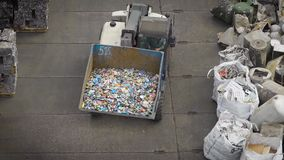 Truck with big scoop sorting trash on yard of recycling factory. View of truck with scoop full of garbage driving between compressed blocks of trash on factory stock footage