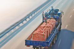 Truck with bricks rides on the road. Top view. Winter day. Tilt shift effect. Construction delivery royalty free stock photos