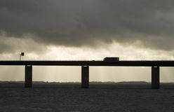 Truck on bridge. Over water in cloudy weather stock photo
