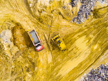 Truck and bulldozer on muddy terrain. Royalty Free Stock Images
