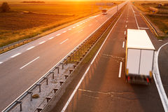 Truck and bus in motion blur at sunset. Truck and bus on highway in motion blur at sunset Royalty Free Stock Photo