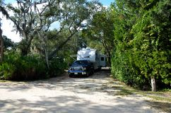 Truck and camper at RV site. Camper and truck at an RV site under the trees Stock Images